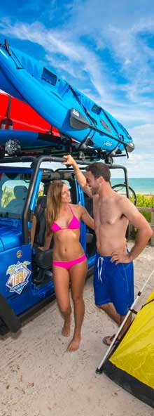 Couple leaning on blue Jeep at the beach