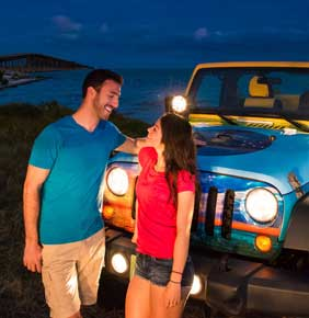 Couple leaning on jeep at night with headlights on