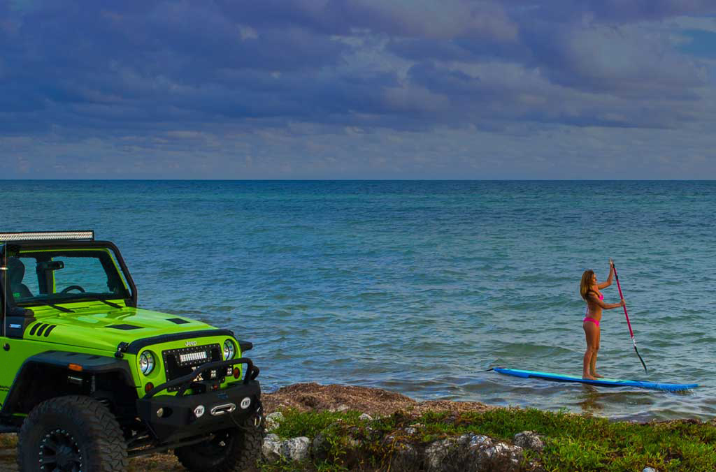 Green jeep on shore and lady kayaking the ocean